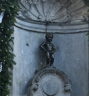 An image of the famous statue The Manneken Pis - a small, naked boy, having a wee.