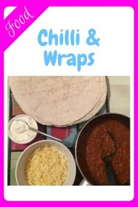 Image showing a pan of chill with some wraps, grated cheese and sour cream accompaniments