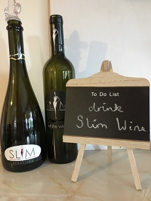 Two bottles of slim wine with a mini chalkboard to do list saying drink slim wine