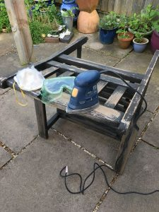 revamp your garden furniture on a budget - a wooden chair being sanded ready for painting